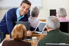 Smiling Teacher Showing Digital Tablet To Senior Students In Cla. Portrait of smiling teacher showing digital tablet to senior students at desk in computer class Stock Image