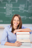 Smiling Teacher With Stack Of Books At Classroom Desk Royalty Free Stock Image