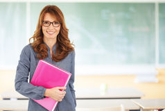 Smiling teacher standing in classroom Royalty Free Stock Photos