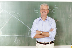 Smiling teacher standing in classroom Royalty Free Stock Images