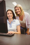Smiling teacher and student behind desk at computer Stock Photography