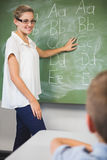 Smiling teacher teaching kids on chalkboard in classroom. At school Stock Image