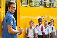 Smiling teacher updating check list of kids while entering in bus Stock Photography