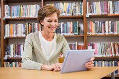 Smiling teacher using tablet pc at library Stock Image