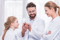 Smiling teachers scientists and student looking at green plant Royalty Free Stock Photos