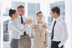 Smiling team of business people clinking their flutes of champagne stock photo