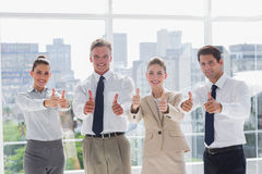 Smiling team of business people giving thumbs up Royalty Free Stock Images