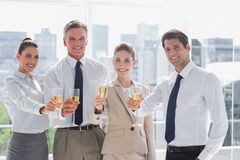 Smiling team of business people honoring a success with champagn Stock Photography