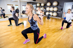 Smiling team doing split squats with weights at fitness gym Stock Photography