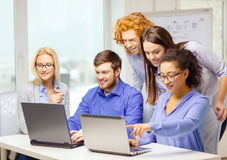 Smiling team with laptop computers in office Royalty Free Stock Photography