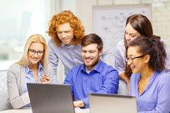 Smiling team with laptop computers in office Royalty Free Stock Images