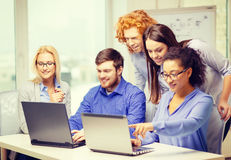 Smiling team with laptop computers in office Stock Photography