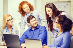 Smiling team with laptop computers in office Stock Images