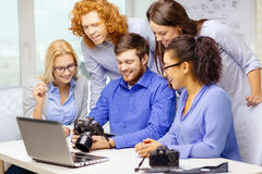 Smiling team with laptop and photocamera in office Stock Images