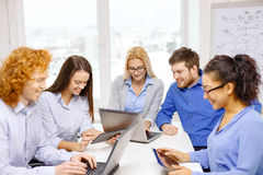 Smiling team with laptop and table pc computers Royalty Free Stock Photos