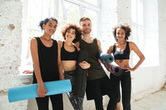 Smiling team looking camera after training. Smiling team of healthy people looking camera after training and holding training mats Royalty Free Stock Image