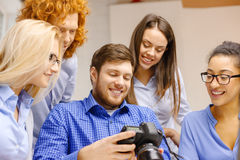 Smiling team with photocamera in office Stock Photo