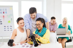 Smiling team with photocamera working in office Royalty Free Stock Images