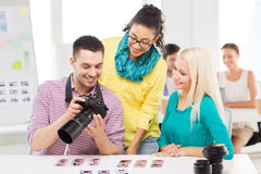 Smiling team with photocamera working in office Stock Photos