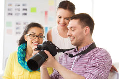 Smiling team with photocamera working in office Royalty Free Stock Photos