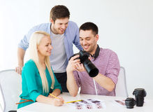 Smiling team with photocamera working in office Stock Image