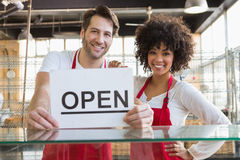 Smiling team posing behind the counter with open sign Stock Photos