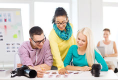 Smiling team with printed photos working in office Stock Photo