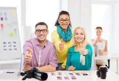 Smiling team with printed photos working in office Stock Photography