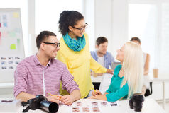 Smiling team with printed photos working in office Stock Photos