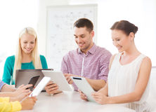 Smiling team with table pc and laptop in office Stock Photography