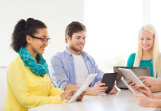 Smiling team with table pc and laptop in office Royalty Free Stock Photo