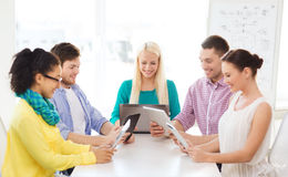 Smiling team with table pc and laptop in office Royalty Free Stock Photography