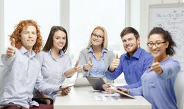 Smiling team with table pc and papers working Stock Photo