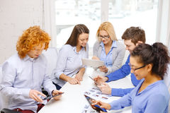 Smiling team with table pc and papers working Stock Photos