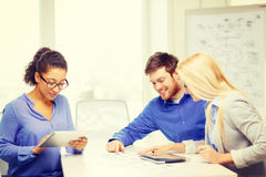 Smiling team with table pc and papers working Stock Images