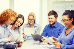 Smiling team with table pc and papers working Royalty Free Stock Photography