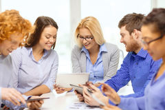 Smiling team with table pc and papers working Royalty Free Stock Photos
