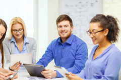 Smiling team with table pc and papers working Stock Photography