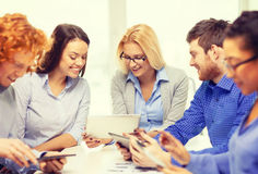 Smiling team with table pc and papers working Royalty Free Stock Images