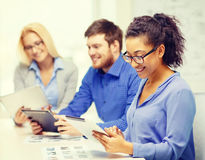 Smiling team with table pc and papers working. Business, office and startup concept - smiling creative team with table pc computers and papers working in office Royalty Free Stock Image