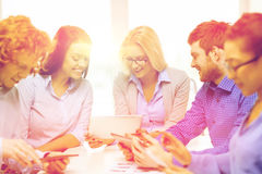 Smiling team with table pc and papers working Royalty Free Stock Image