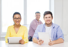 Smiling team with tablet pc computers at office Royalty Free Stock Images