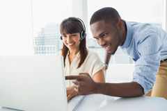 Smiling team using laptop and headset Royalty Free Stock Photos