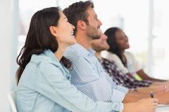 Smiling team of young designers listening at meeting Stock Photography