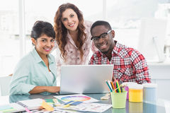 Smiling teamwork with laptop looking at camera Royalty Free Stock Photos