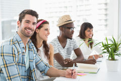 Smiling teamwork listening and taking notes Royalty Free Stock Image