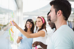 Smiling teamwork reading sticky notes Stock Photo