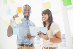Smiling teamwork reading sticky notes and using tablet. In the office Royalty Free Stock Images