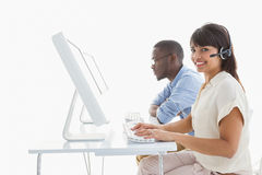 Smiling teamwork using computer and headset Royalty Free Stock Photo