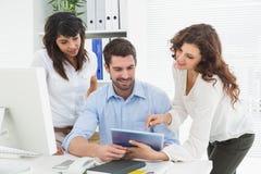 Smiling teamwork using digital tablet Royalty Free Stock Photo
